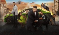 Ryan Reynolds in front of a green car and lots of other actors